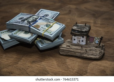 Toy house with a stack of US hundred-dollar bills. The concept of buying real estate.
