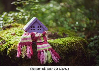 toy house is wrapped in a warm scarf. The concept is warm, cozy, loving, protecting the house. We prepare the house for the cold.