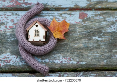Toy house is wrapped in a warm scarf with an autumn leaf. The concept is warm, cozy, loving, protecting the house. We prepare the house for the cold. Space for text