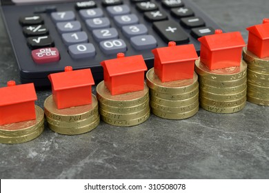 Toy houses on rising stacks of coins, with a calculator in the background.