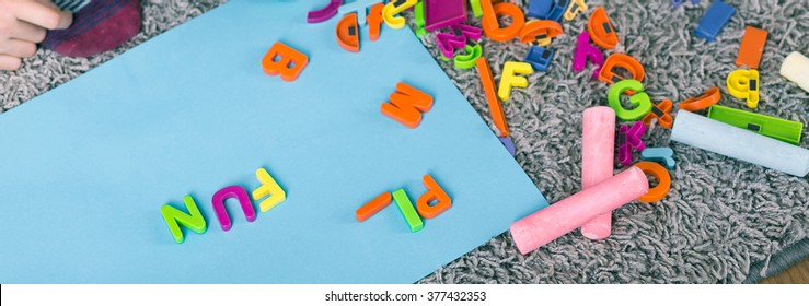 Toy letters and colorful chalk lying on carpet, close up, panorama.
