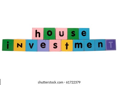 toy letters that spell house investment against a white background with clipping path
