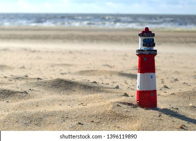 A Toy Lighthouse on the beach in a windy sunny day ,sea in the background