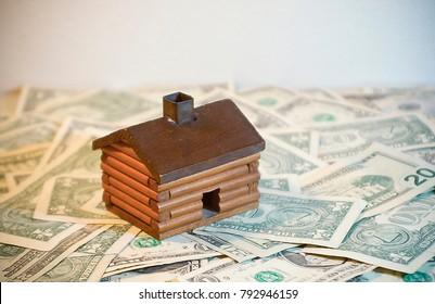 Toy Log Cabin House atop a pile of Money