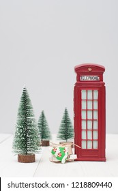 Toy London red phone booth, gifts and christmas trees on light winter background