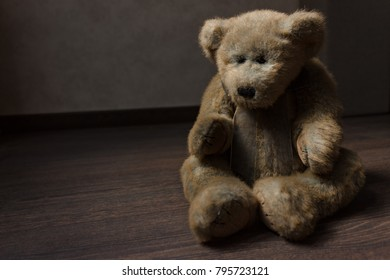 toy of a lonely teddy bear sits on a dark wooden floor