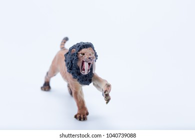 Toy male Smilodon saber-toothed roaring and in attack position with white background