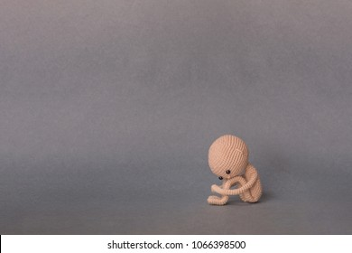 A toy man on a gray background with copy space. Cute amigurumi. Presentation PowerPoint or Keynote. Motivational phrase. A person sits, holding his feet with his hands, sad or crying