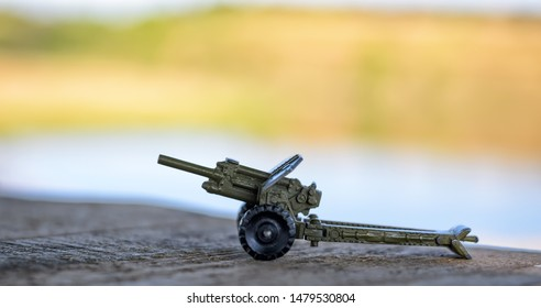 Toy metal artillery cannon (howitzer) standing on a wooden surface, selective focus, blurred background