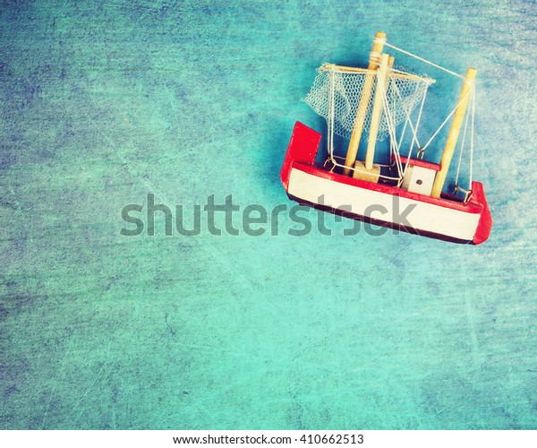 Toy model of ship on old  blue background.