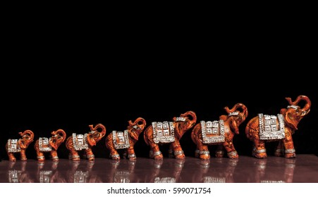 Toy models of elephants standing in a row on black background.