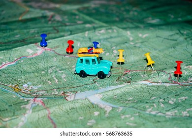 Toy old car rides on a topographic map, the route indicated by the pushpin