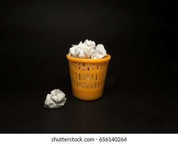 Toy orange dustbin with paper on a black background