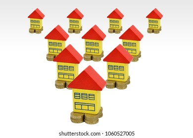 Toy painted houses sitting on coins in a triangular layout. A property investment metaphor.