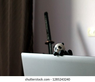 Toy panda is climbing up the laptop cover with the japanese katana on the background