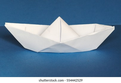 toy paper boat over blue sea background