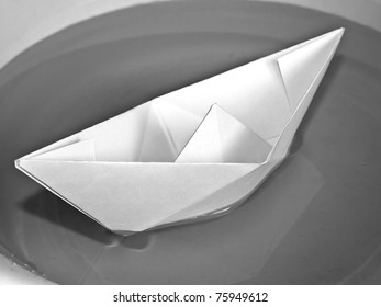 Toy paper boat over a blue water background