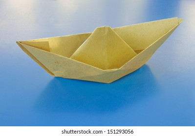 Toy paper boat over a sea blue cardboard