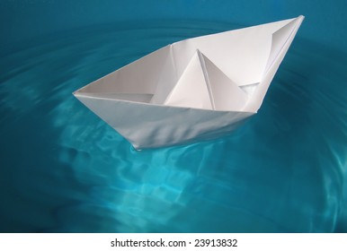 Toy paper ship floating in blue water