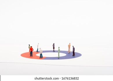 Toy people figures on diagram on white surface isolated on white, concept of disparity