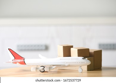 Toy plane and cardboard boxes on table against blurred background, space for text. Courier service