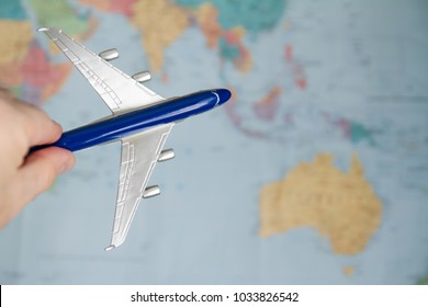 Toy plane in hand on world map background. Aviatransportations. P Sale of tickets for flights. Air travel. Ticket reservation. Traveling by plane. Airline services. Flight to Asia and Australia