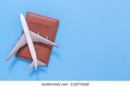 Toy plane on top of passport on blue copy space