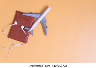 Toy plane on top of passport earphone on Brown copy space