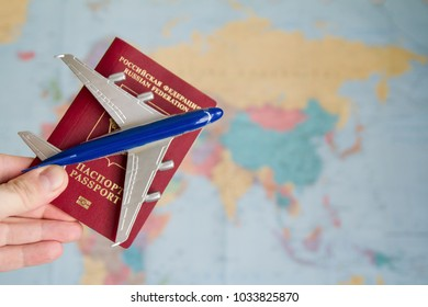 Toy plane and russian passport in hand on world map background. Aviatransportations. Sale of tickets for flights. Air travel. Ticket reservation. Traveling by plane. Airline services.