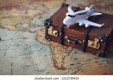 Toy plane and suitcase on vintage map, Travel concept