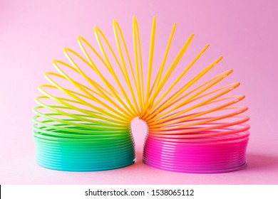Toy plastic rainbow on a pastel pink background. A colored spiral for play and stunts, popular in the 90s.  Minimalism. The concept of toys, childhood. brightness.