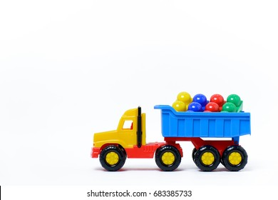 Toy plastic truck with plastic colored cubes isolated on white background