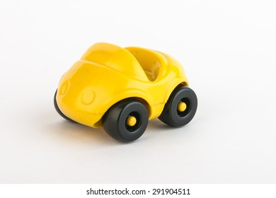 Toy plastic yellow car on white background
