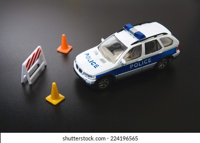 Toy police car and traffic cones, close-up