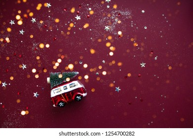 Toy red car with fir tree on the roof . Red background with golden festive lights. Flat lay style. Concept of celebrating new year. Christmas mood.