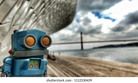 Toy robot on the banks of the Tagus River in Lisbon in a Cloudy day