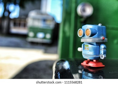 Toy robot on old bus school. Green color in the background.