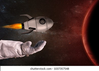 The toy rocket in the hands of the astronaut opposite the red planet. Elements of this image furnished by NASA.