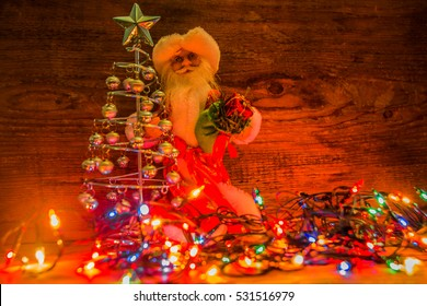 toy of Santa Claus with gifts sack hold in hand  Christmas tree against wooden background. empty copy space for inscription. Christmas and new year background