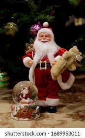 toy Santa Claus and snow globe under the Christmas tree