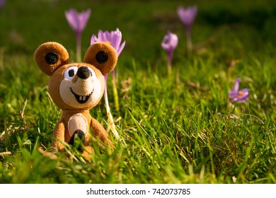 A toy sat down in the grass with flowers.