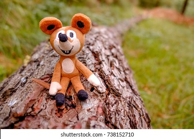 A toy sat in a trunk in an autumn forest.