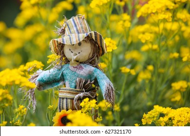 Toy scarecrow against the background of the flower augeratum
