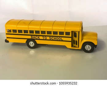 Toy school bus with black signage on a side.