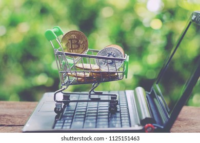 toy shopping cart with bitcoin on notbook, green nature background, saving money for future, ethereum cryptocurrency, blockchain business technology concept