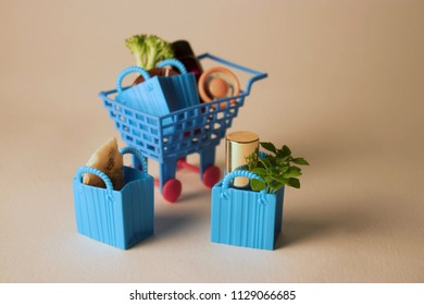 Toy shopping cart full of groceries and house hold items.  Colourful trolley full of fresh vegetables and necessities.