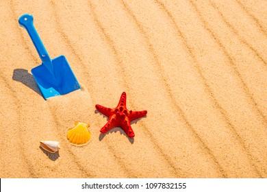 toy, shovel with sea star on a sunny beach