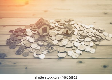 Toy small house standing on a heap of coins. The concept of housing asset
