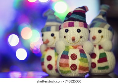 Toy snowman and Christmas lights in the background