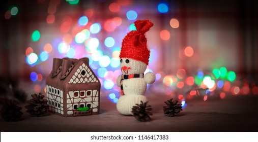 toy snowman and gingerbread house at the Christmas table